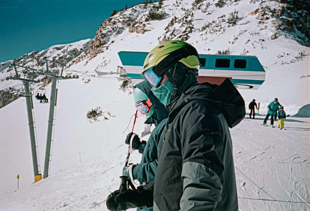 személy fekete kabátot és zöld sisakot - fekete kabátot és zöld sisakot a hóval borított hegyen nappali személy. Hómadár 1 • 09 • 21 Portra 400 35mm. Kis Cottonwood Canyon, Utah, USA (10×7)