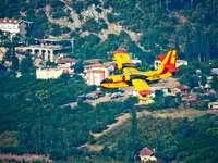 aereo giallo e rosso che sorvola il campo di erba verde
