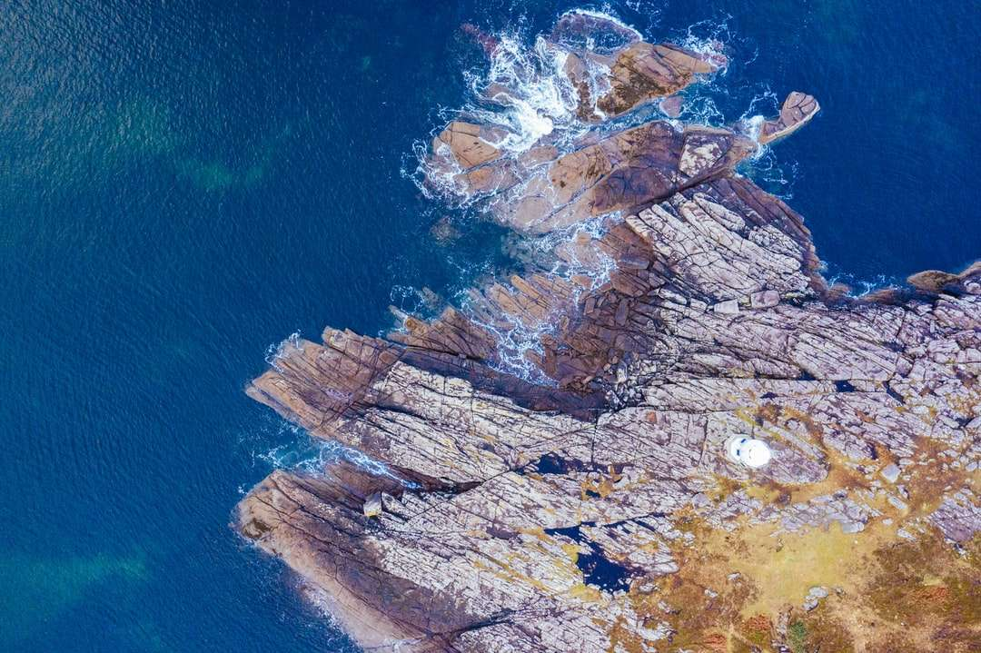 bruine rotsformatie in de buurt van blauwe zee overdag - Schotland van bovenaf. Ullapool, Ullapool, Verenigd Koninkrijk (16×11)