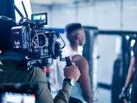 άντρας σε μαύρο σακάκι κρατώντας μαύρη βιντεοκάμερα