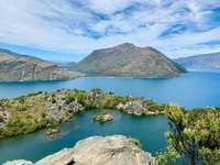 zelená a hnědá hora u jezera pod modrou oblohou