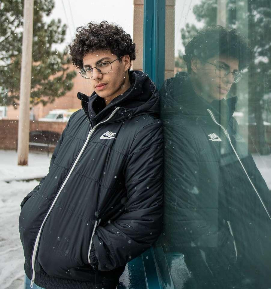 Homme en veste noire debout à côté du récipient en plastique vert - Portrait sous la neige. Suivez @ Ayman.cr2 sur Instagram pour en savoir plus (11×12)
