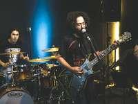 homme en chemise noire jouant de la guitare électrique