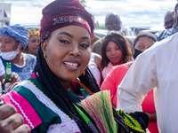 femme souriante en chemise à manches longues blanche et rouge