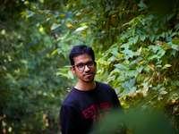 Homme en chemise à col rond noir debout à côté de feuilles vertes