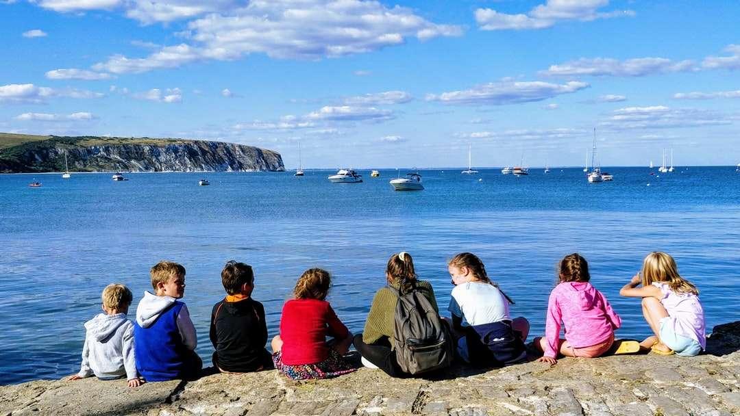 grupa ludzi siedzących na formacji skalnej w pobliżu ciała - grupa ludzi siedzących na formacji skalnej w pobliżu zbiornika wodnego w ciągu dnia. . Studland Bay, Wielka Brytania (12×7)