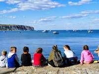 група хора, седнали на скална формация близо до тялото