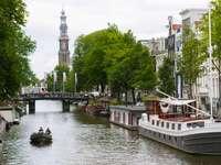 бяла лодка на река близо до зелени дървета и сгради