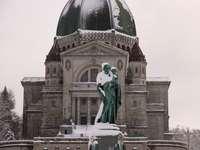 Estatua del hombre delante del edificio de hormigón marrón