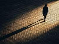 muž v černé bundě na hnědé cihlové podlaze