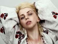 fille en robe à fleurs blanche et rouge allongée sur le lit