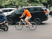 homme en t-shirt orange à cheval sur vélo blanc
