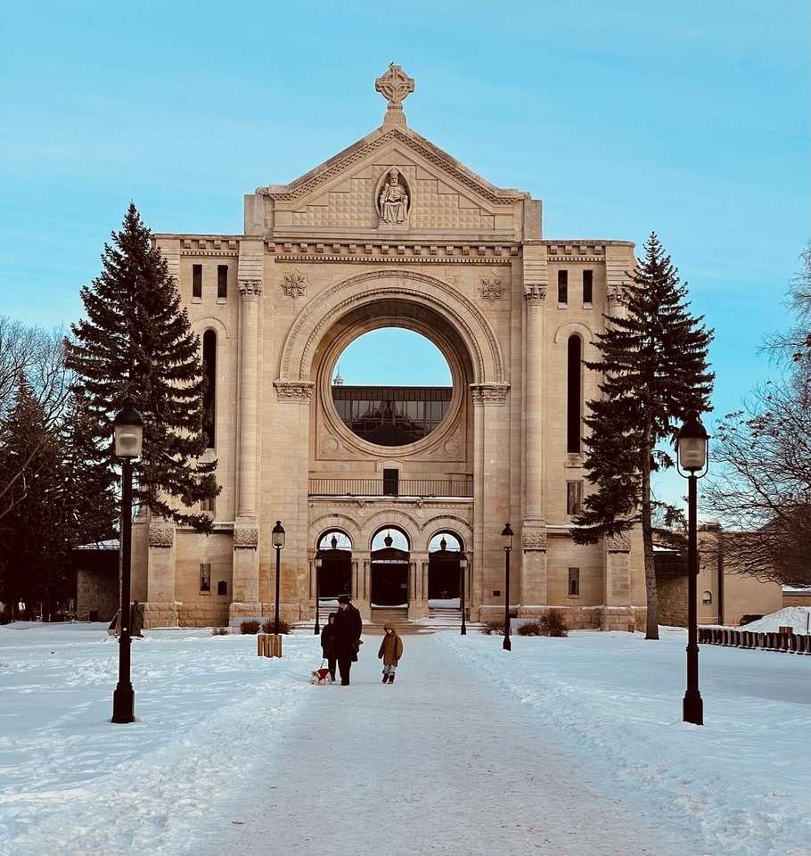 människor som går på snötäckt stig - människor som går på snötäckt stig nära brun betongbyggnad under dagtid. . Avenue de la Cathedrale, Saint Boniface, Winnipeg, MB, Kanada (12×13)