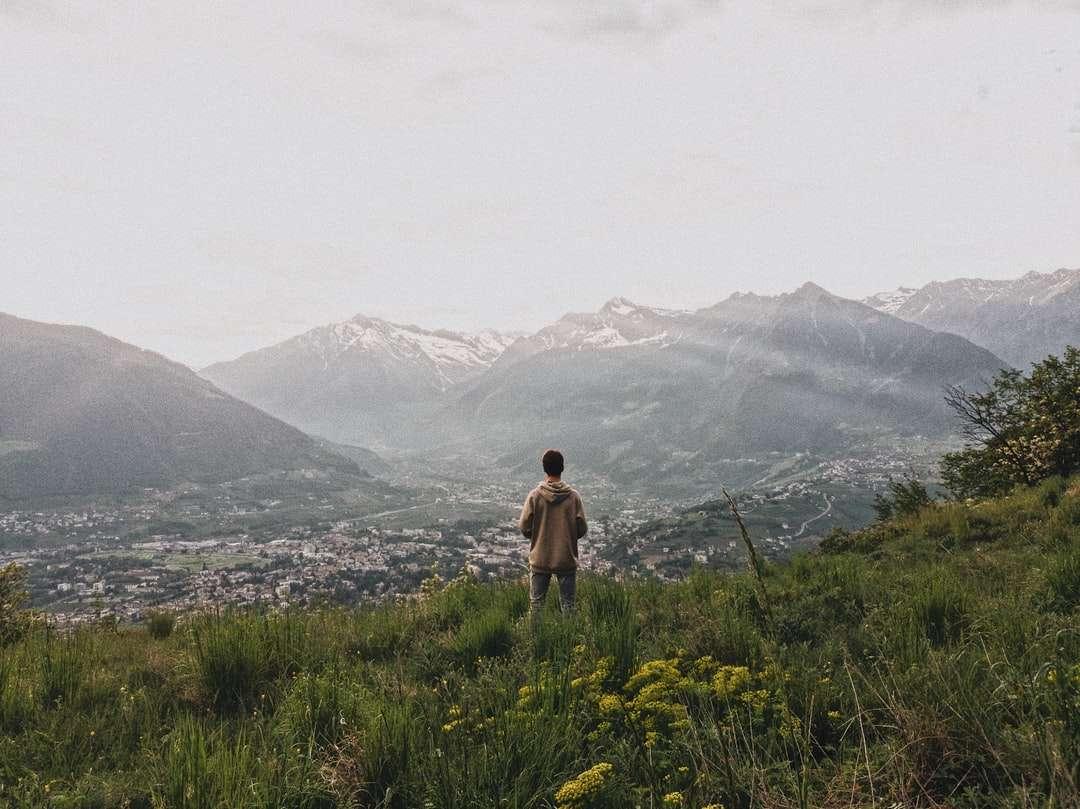 Hombre con camisa marrón de pie sobre el campo de hierba verde - hombre con camisa marrón de pie en el campo de hierba verde durante el día. Vista montañosa (13×10)