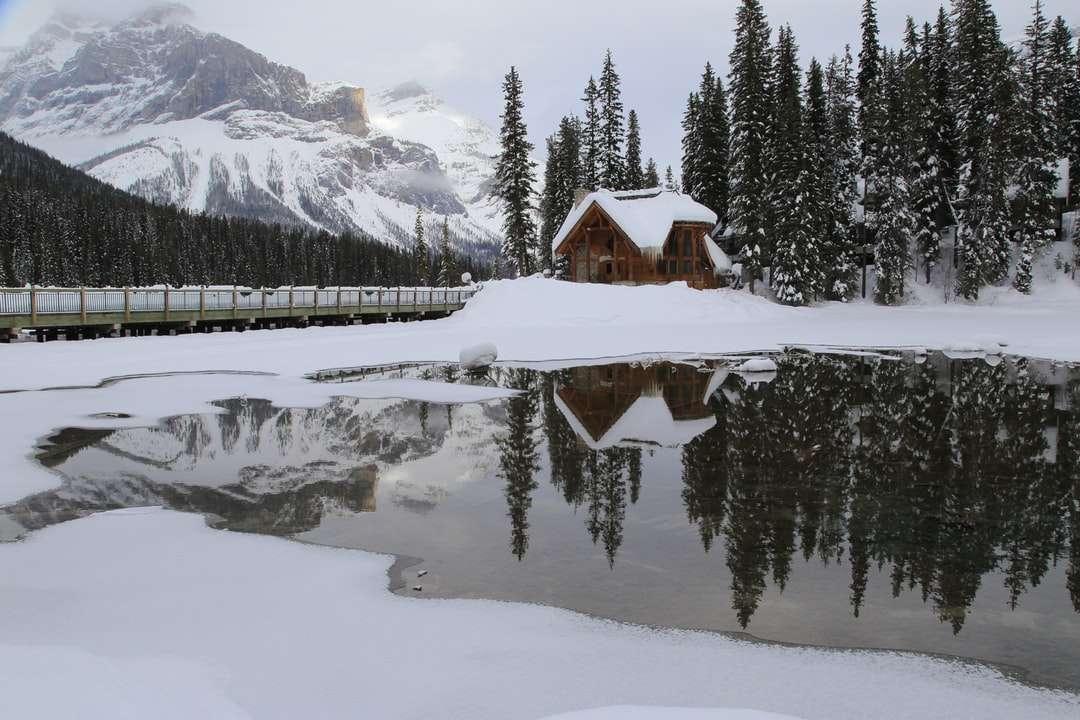 Casa de madera marrón sobre suelo cubierto de nieve - casa de madera marrón en un terreno cubierto de nieve cerca de árboles verdes y montañas cubiertas de nieve durante el día. Emerald Lodge junto a aguas tranquilas (10×7)