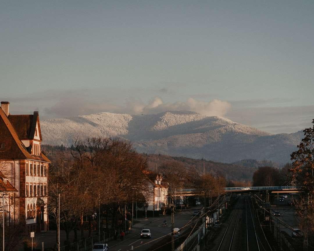 Edificio de hormigón marrón cerca de la carretera durante el día - Montaña nevada en la distancia. Alemania (6×5)