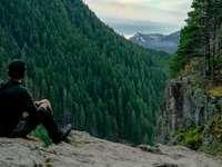 Hombre con chaqueta negra y pantalón negro sentado sobre una roca