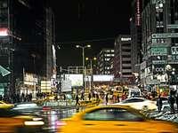 bilar på väg mellan byggnader under natten
