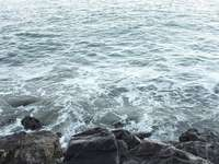 tagsüber schwarze Felsformation neben dem Gewässer