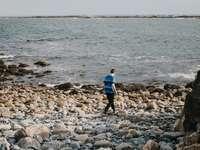момче в синя риза и черни гащи, разхождащо се по скалист бряг