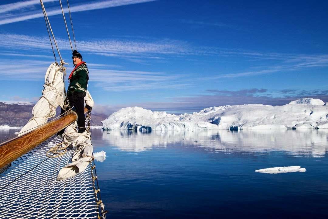 férfi zöld kabát és kék farmer - férfi zöld kabátot és kék farmer farmer barna fa dokkoló állt a hóval borított. . Scoresbysund, Grönland (13×9)