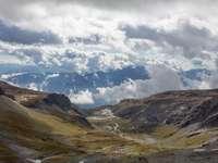 montanhas marrons e verdes sob nuvens brancas e céu azul