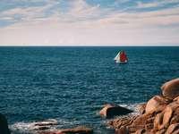 barca a vela bianca sul mare sotto nuvole bianche e cielo blu