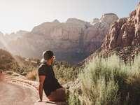 mulher de blusa preta sentada na formação rochosa