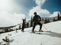 man in black jacket and blue pants riding on ski blades