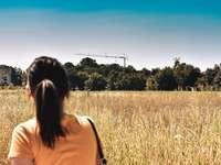 kobieta w żółtym podkoszulku stojącym na brązowym polu trawy