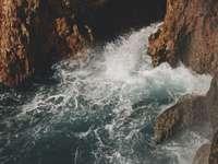 brunt stenigt berg bredvid vattenmassan under dagtid