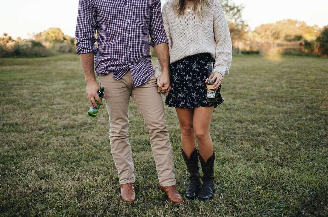 hombre y mujer tomados de la mano mientras camina - hombre y mujer tomados de la mano mientras camina sobre el campo de hierba verde durante el día. Cerrar vista recortada de pareja bebiendo cerveza en un campo (6×4)