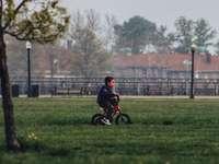 chłopiec w czarnej koszuli, jazda na rowerze na polu zielonej trawie