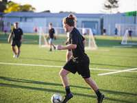 woman in black shirt and shorts playing soccer