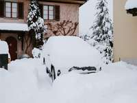 бяла кола, покрита със сняг близо до кафява бетонна сграда