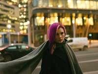 femeie în haina neagră stând pe stradă în timpul nopții