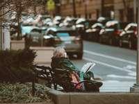 жена в черно яке, седнало на пейката на улицата