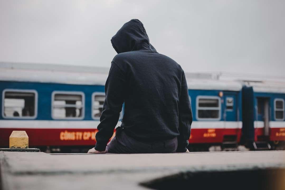 man i svart huvtröja som står nära vitt och rött tåg - man i svart huvtröja som står nära vitt och rött tåg under dagtid (12×8)