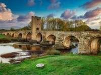Puente de hormigón marrón sobre el río bajo un cielo azul