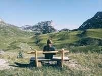жена, седнала на кафява дървена пейка на полето със зелена трева