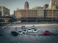 bilar parkerade på parkeringsplats nära brun betongbyggnad