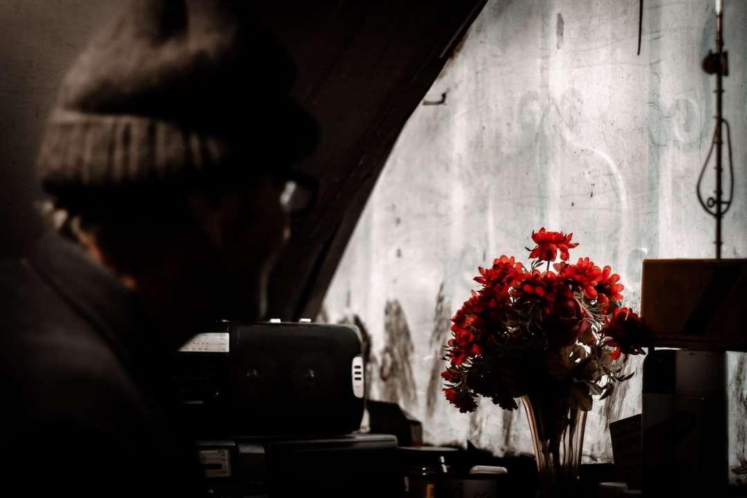 κόκκινα τριαντάφυλλα σε διαφανές γυάλινο βάζο σε καφέ ξύλινο τραπέζι