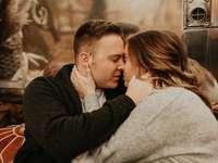 homme en chemise à manches longues noire embrassant la femme