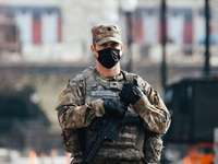 мъж в черно-кафява камуфлажна униформа, държаща пушка