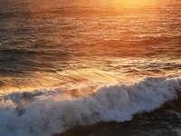 Olas del océano rompiendo en la orilla durante la puesta de sol