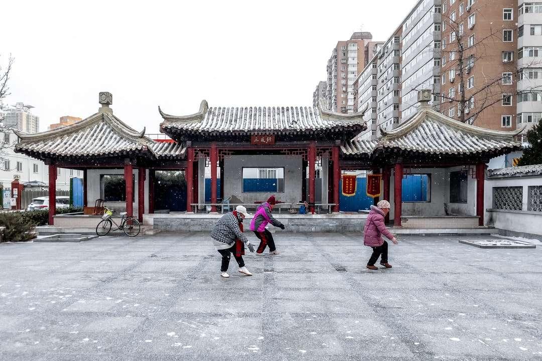 2 mulheres caminhando na rua - 2 mulheres andando na rua perto de edifício de concreto vermelho e branco durante o dia (7×5)