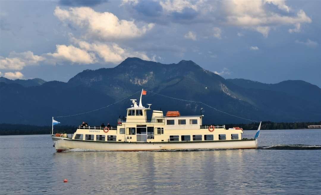 navio branco no mar perto da montanha sob céu nublado - navio branco no mar perto da montanha, sob céu nublado durante o dia. Uma pequena balsa no lago da montanha Chiemsee. Chiemsee, Deutschland (16×10)
