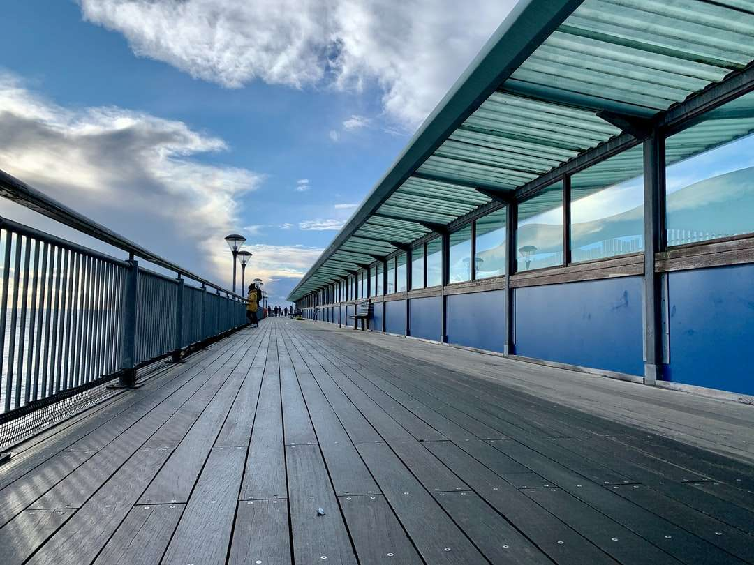 person in black jacket walking on gray wooden dock - person in black jacket walking on gray wooden dock during daytime. I love the rustic feel of an old seaside pier. This leads you to the end of the pier. . Boscombe, Bournemouth, UK (13×10)