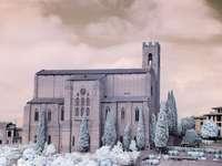 hnědá betonová budova se sněhem pokrytými stromy