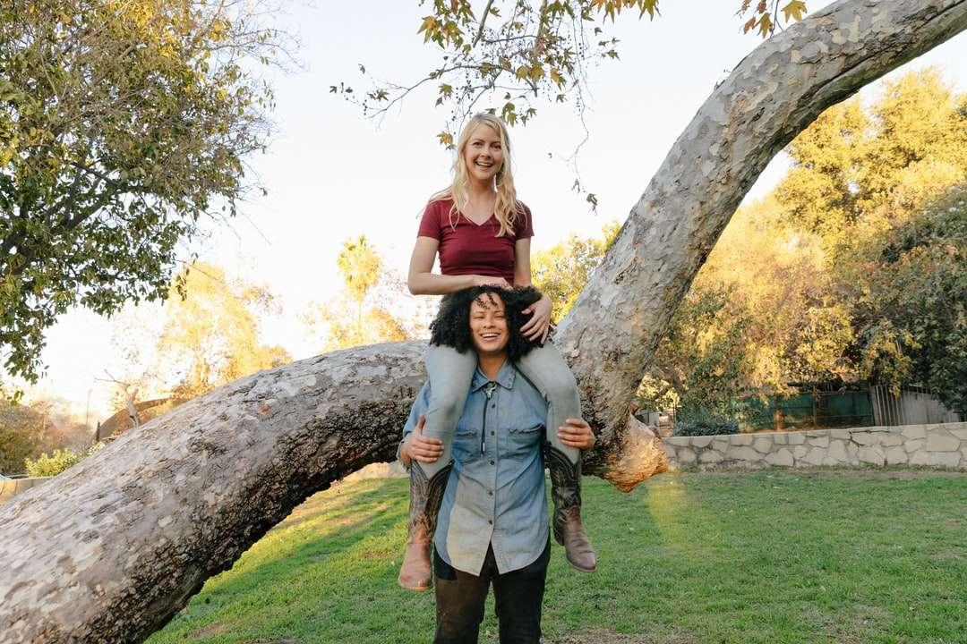 mulher de vestido cinza sem mangas em pé ao lado de árvore marrom - mulher de vestido cinza sem mangas em pé ao lado da árvore marrom durante o dia (6×4)